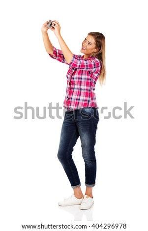 Young smiling woman making a selfie through old photo camera - stock photo