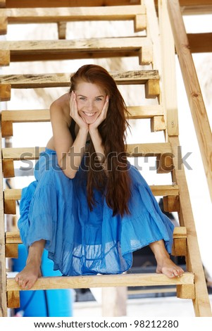 young smiling woman on wooden stairs - stock photo