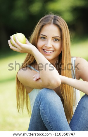Young smiling woman outdoors holding an apple