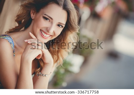 Young smiling woman outdoors portrait. Soft sunny colors.beautiful smiling girl. Woman in the city in summertime. Summer outdoor portrait? Freedom. Beauty. Wind. Sun. - stock photo