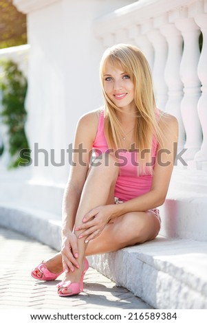 Young smiling woman outdoors portrait. Soft sunny colors.Close portrait. A portrait of a beautiful young Caucasian woman outdoor in the city.  - stock photo