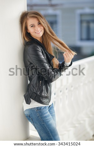 Young smiling woman outdoors portrait. Soft sunny colors.Close portrait. beautiful smiling girl. Woman in the city in summertime. Summer outdoor portrait. Portrait. Woman. Outdoor. Autumn. street. - stock photo