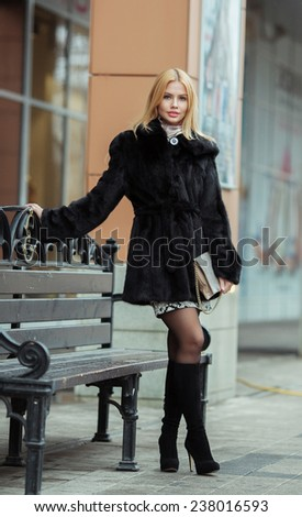 Young smiling woman outdoors portrait. Soft sunny colors.Close portrait. Winter portrait of a beautiful young blonde Caucasian girl with straight hair  outdoors in the city