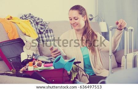 Young smiling woman packing luggage for holidays at home