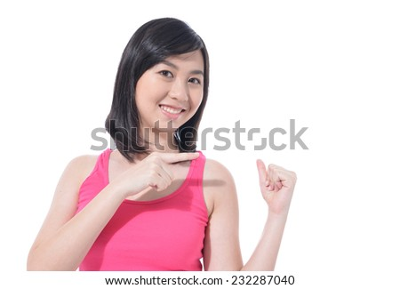 Young smiling woman points a hand with positive facial expression - stock photo