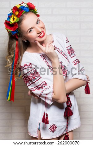 Young smiling woman posing in Ukrainian folk blouse and wreath - stock photo
