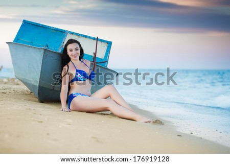 Young smiling woman posing near the boat - stock photo
