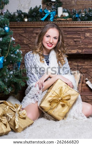 Young smiling woman posing with a golden gift box near the christmas decorations - stock photo
