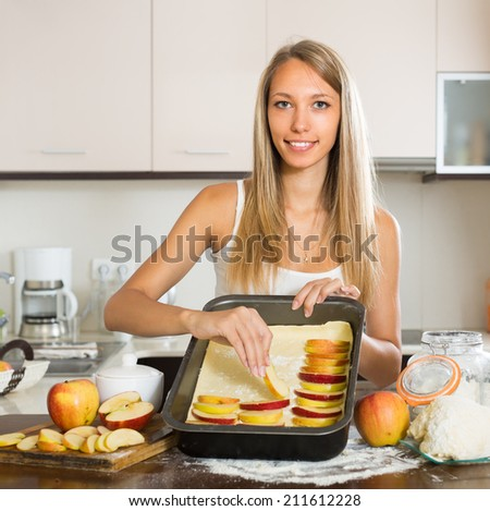 Young smiling woman preparing apple cake in domestic kitchen - stock photo