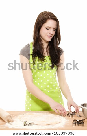 young smiling woman preparing christmas molds for baking with dough on white background - stock photo