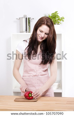 young smiling woman preparing paprika for salad - stock photo