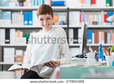 Young smiling woman relaxing and reading a magazine in her office