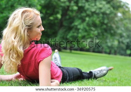 Young smiling woman relaxing in green grass after roller skating - rear view - stock photo