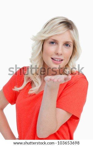 Young smiling woman sending an air kiss against a white background - stock photo