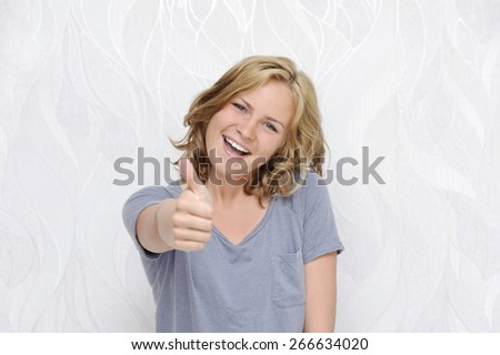 Young smiling woman showing thumbs up - stock photo
