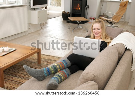 Young smiling woman, sitting in a couch, working on her laptop - stock photo