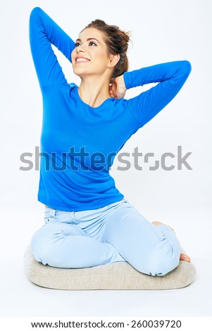 Young smiling woman sitting on mat with hands up. Casual home style portrait. - stock photo
