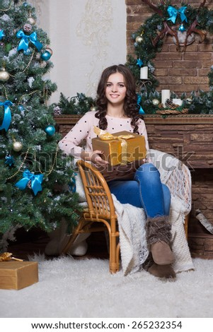 Young smiling woman sitting on the chair and holding a golden gift box - stock photo