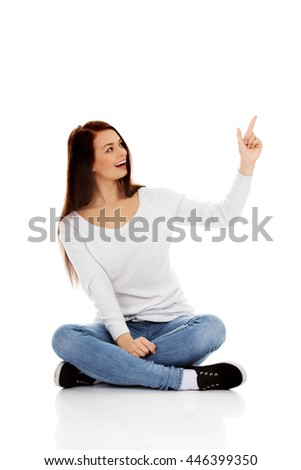 Young smiling woman sitting on the floor and pointing up - stock photo