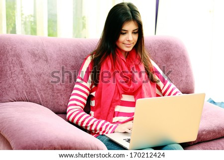 Young smiling woman sitting on the sofa and typing on a laptop - stock photo