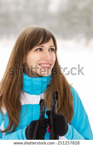 Young smiling woman skiing at the winter outdoor. Pretty caucasian girl looking outside copy space with ski - stock photo