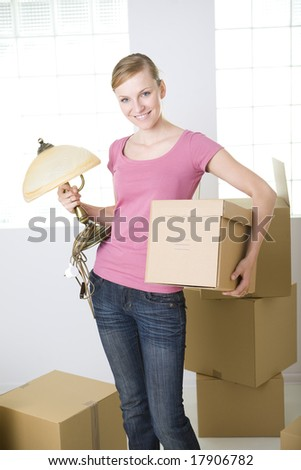 Young smiling woman standing between cardboard boxes. She's holding lamp and box in hands. She's looking at camera.