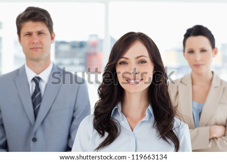 Young smiling woman standing in front of two business people