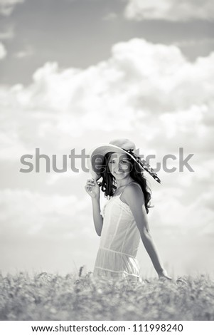Young smiling woman standing in wheat field, black and white,