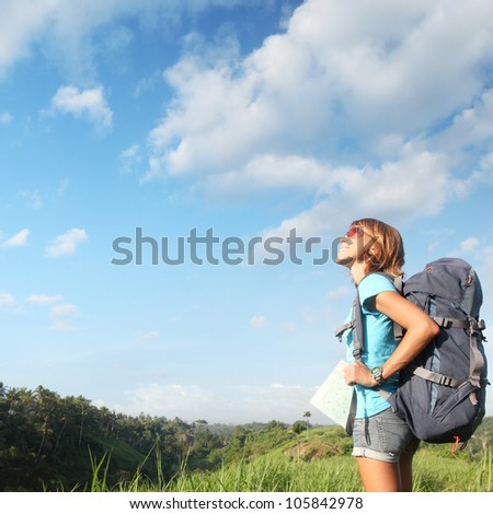 Young smiling woman standing on a green meadow with map and backpack and looking to a blue sky - stock photo