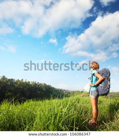 Young smiling woman standing on a green meadow with map and backpack and looking to a blue sky
