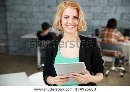 Young smiling woman standing with tablet computer in office