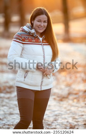 Young smiling woman stands in the winter park in sunset light of sunset sun - stock photo