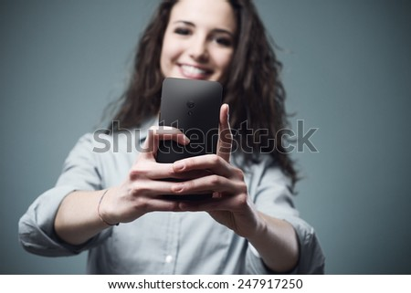 Young smiling woman taking pictures with a mobile touch screen phone - stock photo