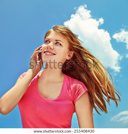 young smiling woman talking on mobile phone on blue sky background - stock photo