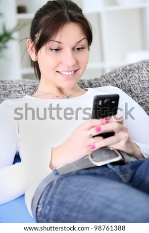 Young smiling woman texting message on smart phone