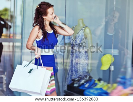 Young smiling woman to purchases talks on cellular telephone. - stock photo