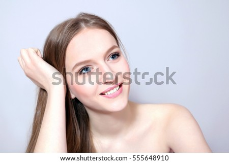 Young smiling woman touching her face  on white background