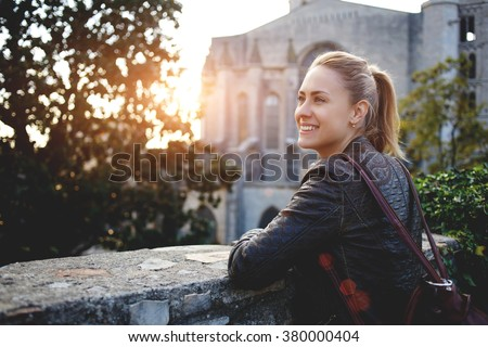 Young smiling woman traveler enjoying town landscape while standing outdoors against big old church, cheerful hipster girl with a rucksack on her back looking at beautiful places from balcony outdoors - stock photo