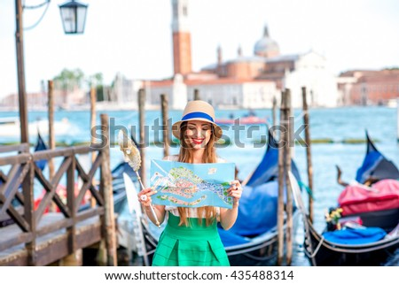 Young smiling woman traveling with paper map standing near San Marco square with gondolas on the background in Venice. - stock photo