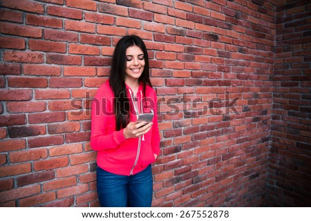 Young smiling woman using smartphone over brick wall.  - stock photo