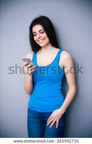 Young smiling woman using smartphone over gray background. Wearing in blue shirt and jeans.  - stock photo