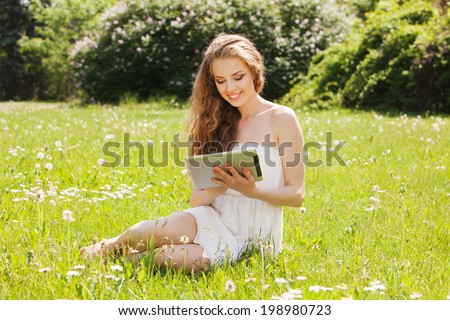 Young smiling woman using tablet outdoor laying on grass