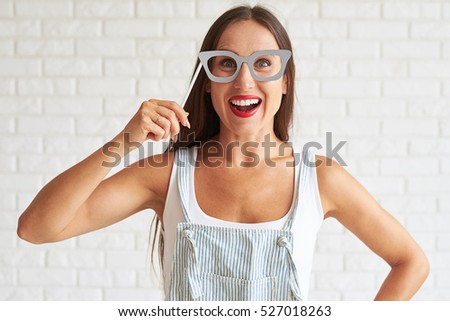 Young smiling woman wear white singlet and holding big glasses-mask, white brick wall on background