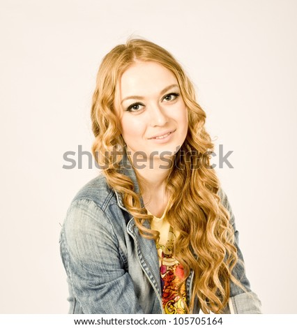 Young smiling woman wearing a denim jacket in studio