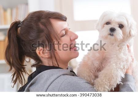 Young, smiling woman wearing deaf aid and holding her little dog - stock photo