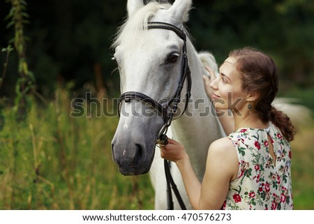 Young smiling woman wearing romantic dress walking with a horse in the forest