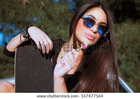 Young smiling woman with a lollipop. Outdoors shot. - stock photo