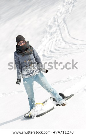 young smiling woman with a sled standing in the deep snow