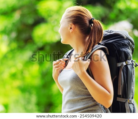 Young smiling woman with backpack in a wood. Hair in a bun. Woman wearing grey clothing. Hiking with camping at summer. - stock photo