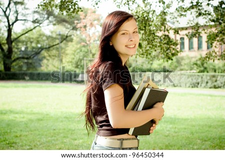 young smiling woman with books outdoors